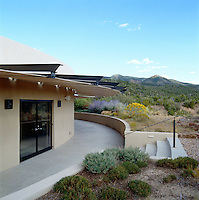 A contemporary adobe house in New Mexico situated near the Sangre de Cristo mountains blends seamlessly with the surrounding landscape