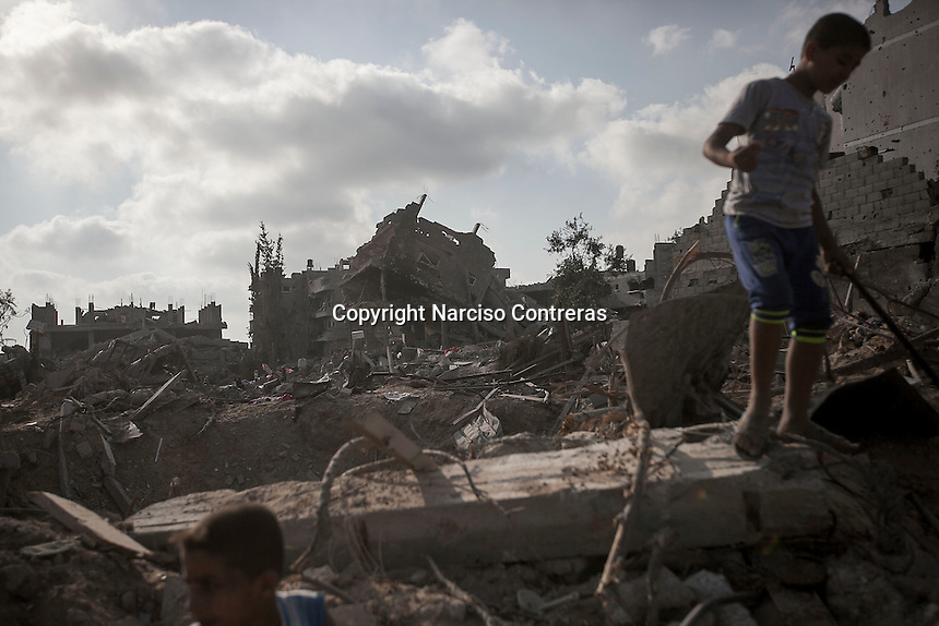 """In this Friday, Aug. 15, 2014 photo, Palestinian children stand over the rubble of their house as they look for their belongings after israeli airstrikes and artillery shelling hit Shuyaja neighborhood during the """"Protective Edge"""" military operation in Gaza City. After a five days truce was declared on 13th August between Hamas and Israel, civilian population went back to what remains from their houses and goods in Gaza Strip. (Photo/Narciso Contreras)"""