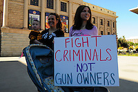 """Phoenix, Arizona. January 19, 2013 - A demonstrator hold a sign asking the federal government to go against criminals not guns owners. The rally to support gun rights took place in front of the historic Arizona Capitol. As President Barack Obama proposed new gun regulations last week, gun owners demonstrated against it with national """"Guns Across America"""" rallies to defend the Second Amendment. Dozens showed up at the Arizona State Capitol, many of them carrying weapons. Photo by Eduardo Barraza © 2013"""