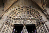 View from below of the portal of the upper chapel of La Sainte-Chapelle (The Holy Chapel), 1248, Paris, France. The upper chapel portal is protected by a porch. Its tympanum represents the Last Judgement. Christ in majesty is surrounded by angels holding torture instruments. On the lintel, angels call dead souls to rise from their graves. In the middle, Archangel Michael proceeds to the weighing of the souls while a devil is trying to cheat. The trumeau is decorated by a statue of the Christ blessing the crowds. La Sainte-Chapelle was commissioned by King Louis IX of France to house his collection of Passion Relics, including the Crown of Thorns, and is considered among the highest achievements of the Rayonnant period of Gothic architecture. Picture by Manuel Cohen