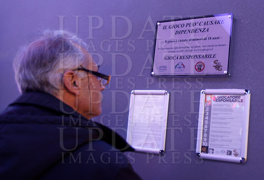 Un uomo all'interno del Dubai Palace, in occasione della sua inaugurazione, a Roma, 2 marzo 2013.<br /> A man reads a sign reading &quot;Gamble can cause dependance. Play responsible&quot; at the Dubai Palace gameroom, on the occasion of its inauguration in Rome, 2 March 2013.<br /> UPDATE IMAGES PRESS/Riccardo De Luca