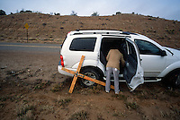 Fred Garcia, 68, of Albuquerque, N.M., stops for water at the van of a family member enroute to the Santuário de Chimayó in northern New Mexico on Good Friday. Thousands of pilgrims make a pilgrimage to the 190-year-old shrine every Easter as an expression of faith, a connection to old Hispanic roots and in hopes of the miracles reputed to occur there. Garcia has been carrying the same cross for 25 years.<br />