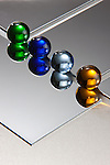 Colored glass marbles sit atop a polished diagonal metal surfaces.  Each of the marbles is reflected.