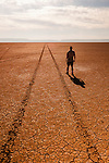 A man stands next to a set of tire tracks stretching off into the distance on the dry lake bed playa of the Alvord Desert in Southeast Oregon.