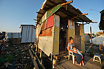 """A woman sits with her daughter outside her temporary house in Tacloban, a city in the Philippines province of Leyte that was hit hard by Typhoon Haiyan in November 2013. The storm was known locally as Yolanda. The house sits within the 40 meter """"no build"""" zone in which the government has prohibited construction of houses."""