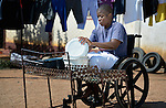Caroline Mandishona washes dishes at her home in Bulawayo, Zimbabwe. Mandishona suffered cerebral palsy and uses a wheelchair provided by the Jairos Jiri Association with support from CBM-US.