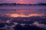 Sunrise in fog Lake Cassidy with Mount Pilchuck reflection in water with clouds Snohomish County Washington State USA