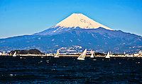 Snow capped Mt. Fuji in brilliant sunshine with sailing boats.