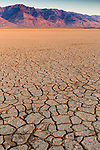 The sun rises above the distant hills looking over the dry, fractured soil of the Alvord Desert in Southeast Oregon.