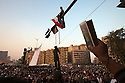 An Egyptian protester hangs an effigy of Egyptian Army Field Marshall Hussein Tantawi from a lightpost over Tahrir Square during a million man march against military rule November 22, 2011 in central Cairo, Egypt. Thousands of protesters demanding the military cede power to a civilian government authority clashed with Egyptian security forces for a fourth straight day in Cairo, with hundreds injured and at least 29 protestors killed so far.  (Photo by Scott Nelson)