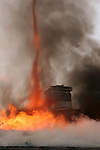 Flames forming a tornado of heat and smoke from the roof of a house fire