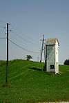 Old stone lookout tower with metal gabbled roof, used fas electrical substations in fields. Aschaffenburg area, Bavaria, Germany.