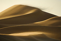 A Namib Desert sand dune on the move, being eroded by the powerful force of desert winds that gradually push the dunes in a north-westerly direction, Namibia.