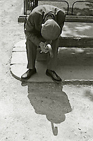 An old man with a flat cap and walking stick sits, head bowed, on a bench in a Barcelona park.