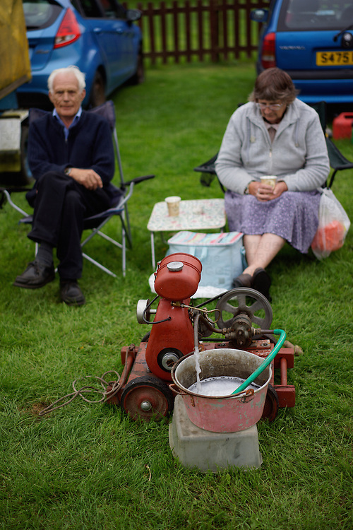 Elderly couple sitting on camping stools demonstrating their 1955 water pump