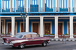 Havana, Cuba; a red and white 1957 Chevy Bel Air parked in front of the Hotel Telegrafo, along Paseo de Marti, in early morning soft light