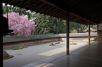 A view of the carefully raked gravel of the Ryoan-Ji Temple and the trees beyond from a corner of the long veranda