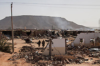Stateless people of Malian origin collect their belongings from the rubble in the Tinkineien neighbourhood of Awbari City. The area was shattered by heavy shelling prior to the ceasefire that was instigated just a few days before.