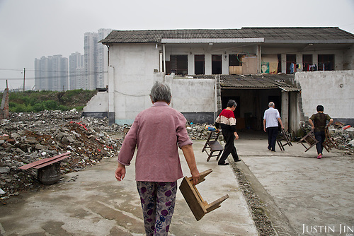 Elderly people in southern China walk to their home that is about to be demolished for modern high rise. <br /> <br /> China is pushing ahead with a dramatic, history-making plan to move 100 million rural residents into towns and cities over six years &mdash; but without a clear idea of how to pay for the gargantuan undertaking or whether the farmers involved want to move.<br /> <br /> Moving farmers to urban areas is touted as a way of changing China&rsquo;s economic structure, with growth based on domestic demand for products instead of exporting them. In theory, new urbanites mean vast new opportunities for construction firms, public transportation, utilities and appliance makers, and a break from the cycle of farmers consuming only what they produce.<br /> <br /> Urbanization has already proven to be one of the most wrenching changes in China&rsquo;s 35 years of economic reforms. Land disputes rising from urbanization account for tens of thousands of protests each year.
