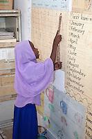 Jambiani, Zanzibar, Tanzania.  African Muslim Schoolgirl Reciting Numbers on a Wall Chart.
