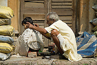 A young boy gets a haircut from a street-side barber in Kolkata, India.