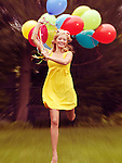 Happy young woman in summer dress running with colorful balloons