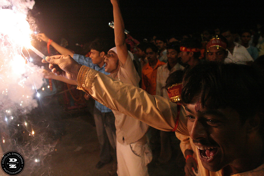 Hindu pilgrims light fireworks around an idol of the Goddess Durga before taking her on a boat to be immersed in the Ganges (Ganga) River in  Varanasi, India during the festival of Dussehra.  On the tenth day after Navaratri (usually in September or October) is the Hindu  festival of Dussehra / Vijay Dashmi.  The immersion of the Goddess Durga symbolizes  the end of the goddess? brief visit to the earth. Photograph by Douglas ZImmerman..