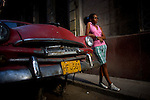 portrait of teen leaning against old chevy in the streets of havana, cuba