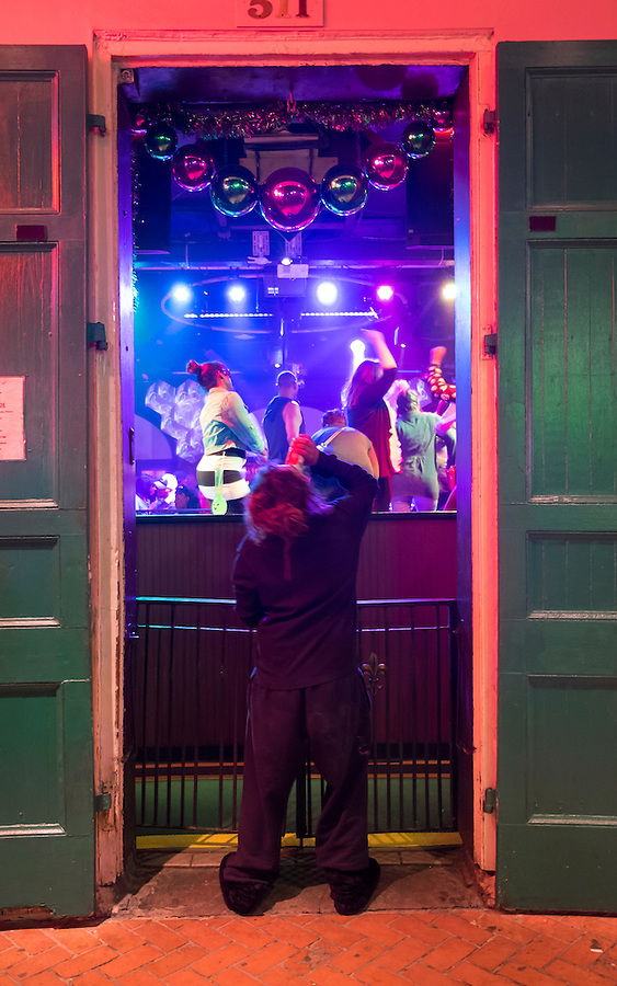 NEW ORLEANS - CIRCA FEBRUARY 2014: Woman drinking a beer in front of a nightclub during Mardi Gras celebrations in the French Quarter in New Orleans