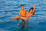 Couple playing in the ocean splashing towards the camera.  He's holding her in his arms.
