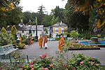 "Portmeirion, in North Wales, is a resort, where no one has ever lived. A self-taught Welsh architect named Sir Clough Williams-Ellis built it out of architectural salvage between the 1920s and 1970s, loosely based on his memories of trips to Portofino. Including a pagoda-shaped Chinoiserie gazebo, some Gothic obelisks, eucalyptus groves, a crenellated castle, a Mediterranean bell tower, a Jacobean town hall, and an Art Deco cylindrical watchtower. He kept improving Portmeirion until his death in 1978, age 94. It faces an estuary where at low tide one can walk across the sands and look out to sea. At high tide, the sea is lapping onto the shores. Every building in the village is either a shop, restaurant, hotel or self-catering accomodation. The village is booked out at high season, with numerous wedding receptions at the weekends. Very popular amongst the English and Welsh holidaymakers. Many who return to the same abode season after season. Hundreds of tourists visit every day, walking around the ornamental gardens, cobblestone paths, and shopping, eating ice-creams, or walking along the woodland and coastal paths, amongst a colourful assortment of hydrangea, rhododendrons, tree ferns and redwoods. The resort boasts two high class hotels, a la carte menus, a swimming pool, a lifesize concrete boat, topiary, pools and wishing wells. The creator describes the resort as ""a home for fallen buildings,"" and its ragged skyline and playful narrow passageways which were meant to provide ""more fun for more people."" It does just that.///Buddhist monks from Lichfield are tourists in Portmeirion. Ornamental central gardens of Portmeirion village. Flanked by Dome Gallery, Gothic tower, Renaissance collonades, with lwans, flowerbeds, topiary, pools and fountains."