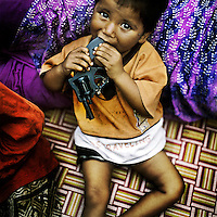 A boy in the Kathputli Colony plays with his toy gun. Located in northwest Delhi, Kathputli is inhabited by approximately 2,000 performing artists, practicing traditional art forms such as marionette puppetry, juggling, magic, acrobatics, dance and music. Many have travelled all over the world showcasing their abilities, but they still choose to remain living in this slum, which is one of the most impoverished in the city.