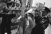 Police remove an old gentleman carrying a huge wooden crucifix from infront of the American embassy where he had been protesting against the war in Iraq. Tokyo, japan.