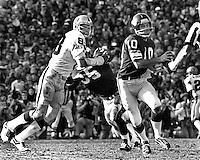 Minnesota Vikings QB Fran Tarkenton scrambles away from Oakland Raider linebacker Ted Hendricks. 1977 Super Bowl..  (photo by Ron Riesterer)