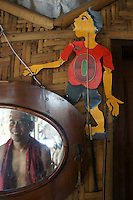 decoration in a cafe near water castle, the owner giving a smile in the mirror, next to a modern interpretation of  wayang kulit (leather puppet), Yogyakarta, island Java, archipelago of Indonesia,  September 2011