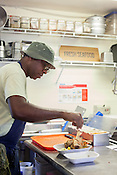 Copyright Justin Cook | September 26, 2013 - Ricky Moore seasons an order at Saltbox Seafood Joint.