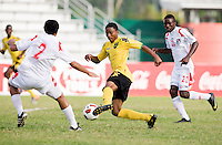 Jevani Brown (14) of Jamaica carries the ball past Eric Francisco (2) of Panama during the third place game of the CONCACAF Men's Under 17 Championship at Catherine Hall Stadium in Montego Bay, Jamaica. Panama defeated Jamaica, 1-0.