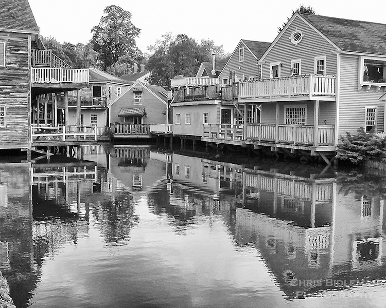 Several houses are seen reflected in water of smooth, calm water during Fall in Kennebunkport, Maine in a black and white (B&W) photo rendering
