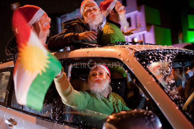 IRAQ, SULAIMANIYAH:  Revelers dressed as Baba Noel (Santa Claus or Father Christmas) and waving the Kurdish flag ride down Salim street in Sulaimaniyah...Revelers brought in the new year all across Kurdistan with shows of fireworks and enormous street parties...Photo by Metrography