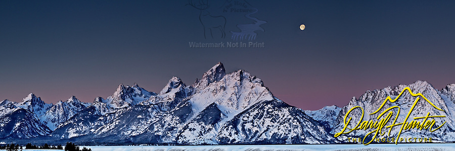 Full moon at sunrise over the Grand Tetons from the Snake River Overlook in Grand Teton National Park