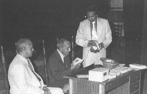 José Rafael Lantigua, de pie, entregándole al poeta Domingo Moreno Jiménes (al centro), el primer ejemplar de su obra Apóstol de la Poesía, 1976