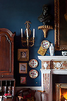 Gilt-framed portraits and a collection of porcelain plates are displayed on the walls of the living room
