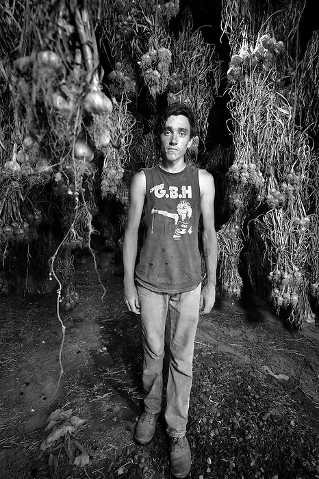 A young farmer standing amongst drying garlic hanging in a barn