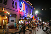 Crowds walk up and down past the bright neon lights of Austin famous 6th Street bar & party district. The nine-block area of East Sixth Street roughly between Lavaca Street to the west and Interstate 35 to the east is recognized as the Sixth Street Historic District and was listed in the National Register of Historic Places on December 30, 1975. Developed as one of Austin's trade and commercial districts in the late 1800s, the predominant building style are two- or three-story masonry Victorian commercial architecture.