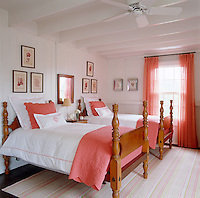 Framed seashell prints hang above the antique beds in this comfortable twin bedroom.