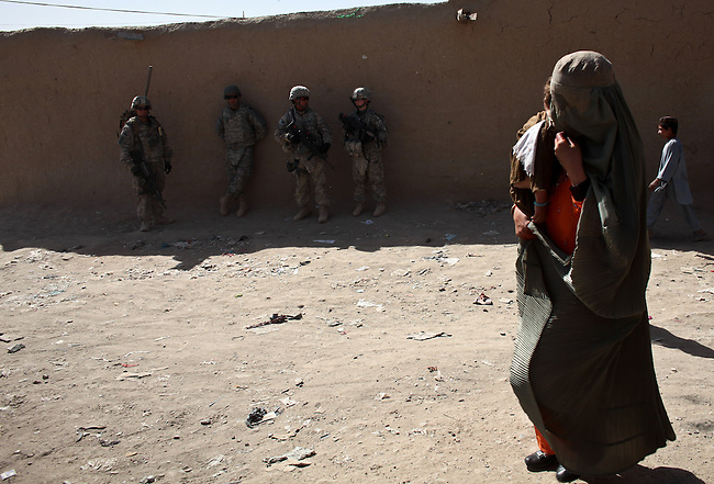 An Afghan woman wearing a burqa and carrying a child walks past U.S. soldiers resting in the shade while on patrol in Kandahar, Afghanistan. Oct. 17, 2010. DREW BROWN/STARS AND STRIPES