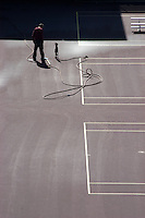 A man makes repairs to a tennis court with a pneumatic tool