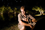 Guido Westhoff handles an olive python (Liasis olivaceus) at night with background eucalyptus trees illuminated