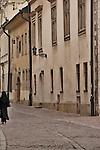 A nun walks down a cobble stone street in Krakow, Poland