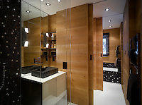 Sliding wooden doors separate the bath from the shower in this sleek modern bathroom